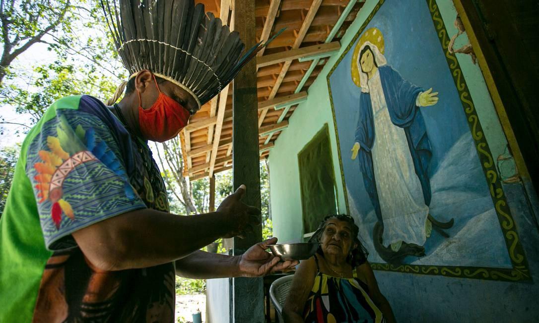 O chefe Leno da tribo Kunaruara entrega um remédio natural com infusão de mel a um residente em sua vila ao lado do rio Tapajós, no município de Santarém Foto: TARSO SARRAF / AFP