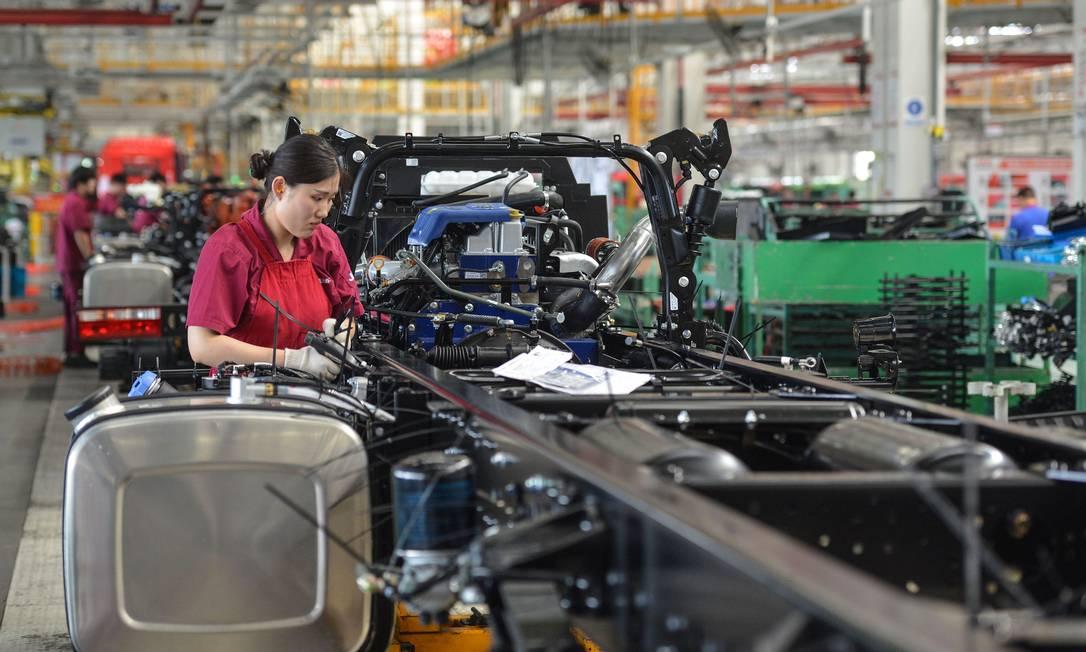 Uma funcionária trabalha em uma linha de montagem de caminhões em uma fábrica em Fuyang, na província de Anhui, leste da China, em 16 de julho de 2020 (Foto de STR / AFP) Foto: STR / AFP