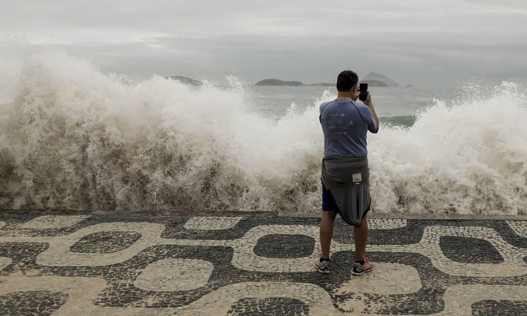Homem fotografa ondas atingindo o calçadão do Leblon, na Zona Sul do Rio Foto: Gabriel de Paiva / Agência O Globo