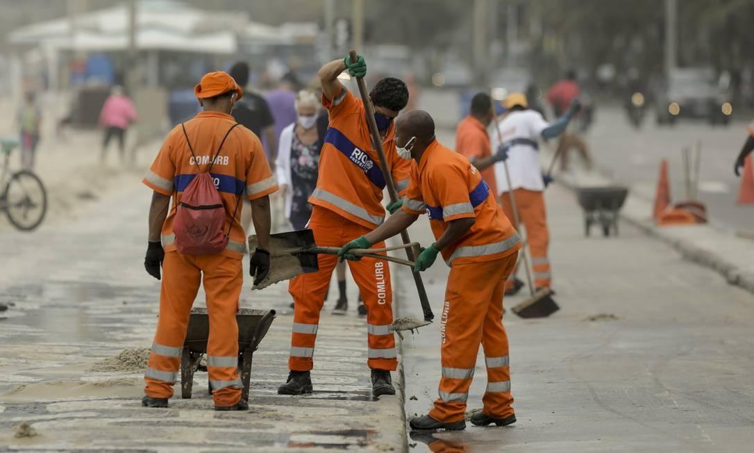 Servidores da Comlurb trabalham para limpar o calçadão que recebeu sedimentos transportados pelo mar Foto: Gabriel de Paiva / Agência O Globo