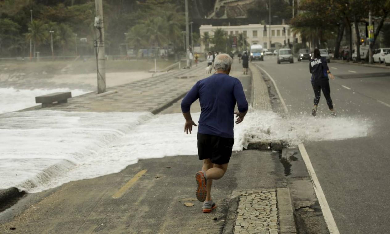 Homem que pratica corrida na orla desvia do mar que cobre a ciclovia no Leblon Foto: Gabriel de Paiva / Agência O Globo