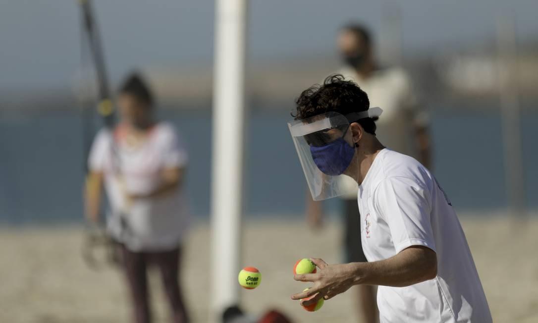 Homem pratica tênis de praia usando máscara protetora e escudo facial, em Ipanema Foto: Gabriel de Paiva / Agência O Globo
