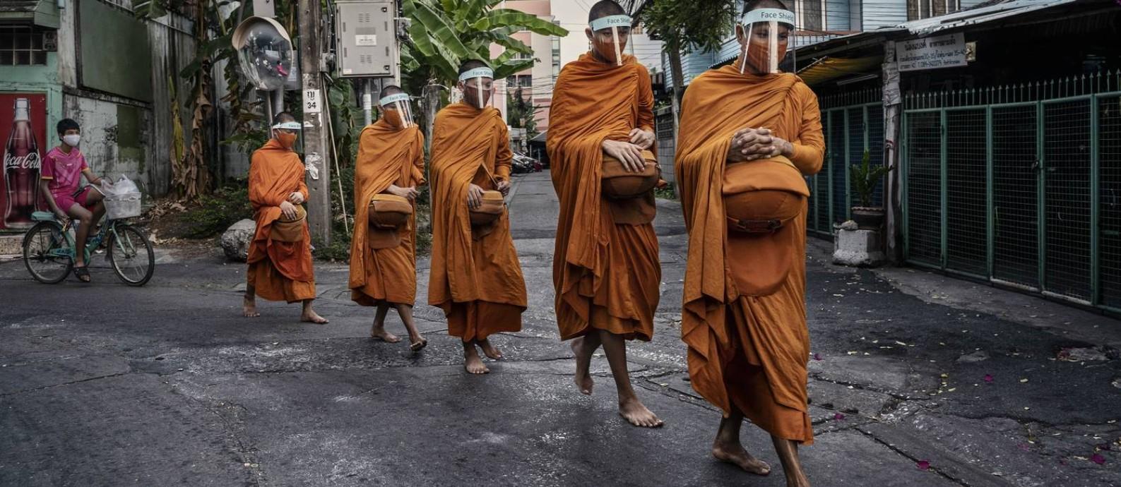 Monges tailandeses usam máscara e viseira para se protegerem da Covid-19 Foto: ADAM DEAN / NYTN