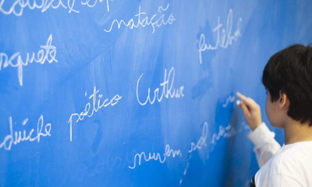 Aluno escreve no quadro: prefeito não considera prudente a retomada às vésperas do recesso escolar Foto: Fernando Donasci / Fernando Donasci/Agência O Globo