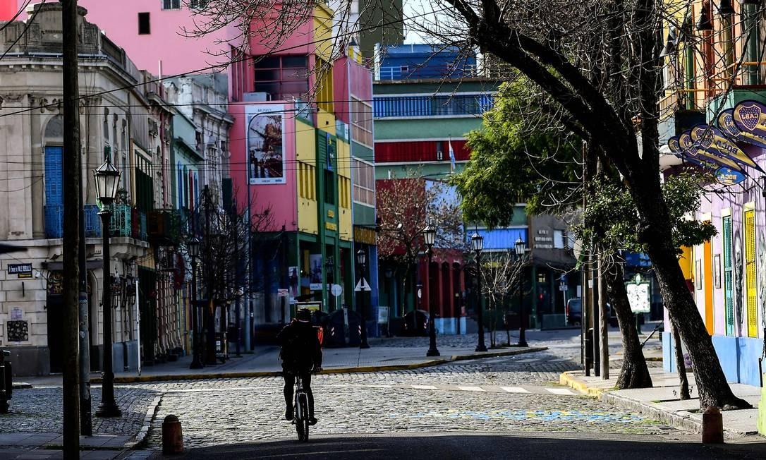 Homem pedala pelas ruas vazias de La Boca, em Buenos Aires Foto: RONALDO SCHEMIDT / AFP