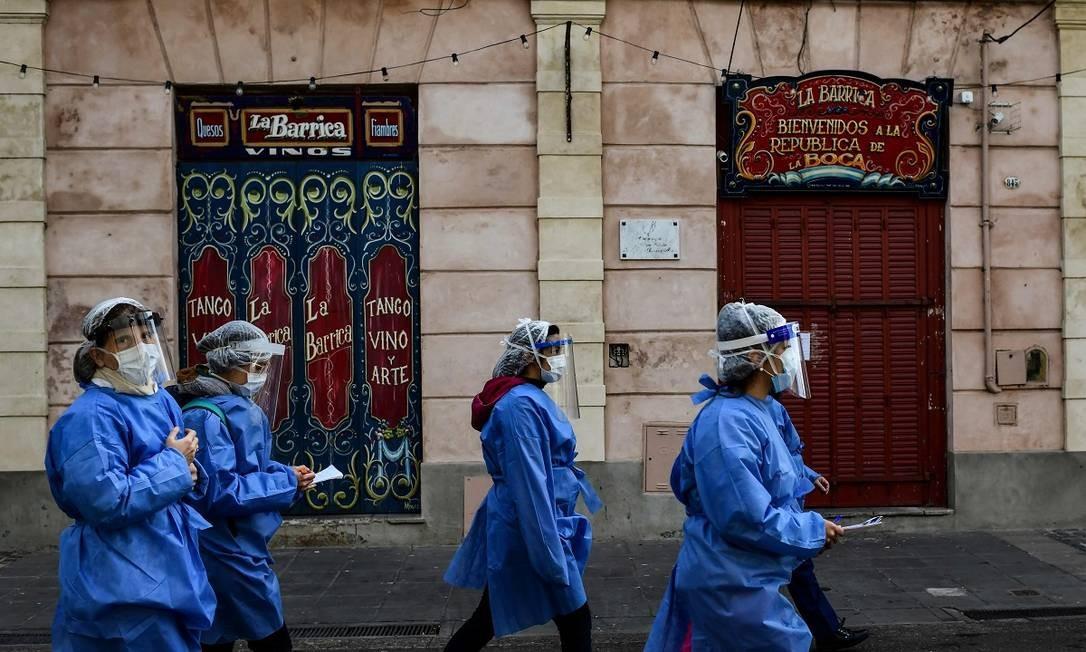 Profissionais de saúde caminham pelo deserto Caminito, no bairro de La Boca, passando em frente a lojas de suvenires fechadas Foto: RONALDO SCHEMIDT / AFP