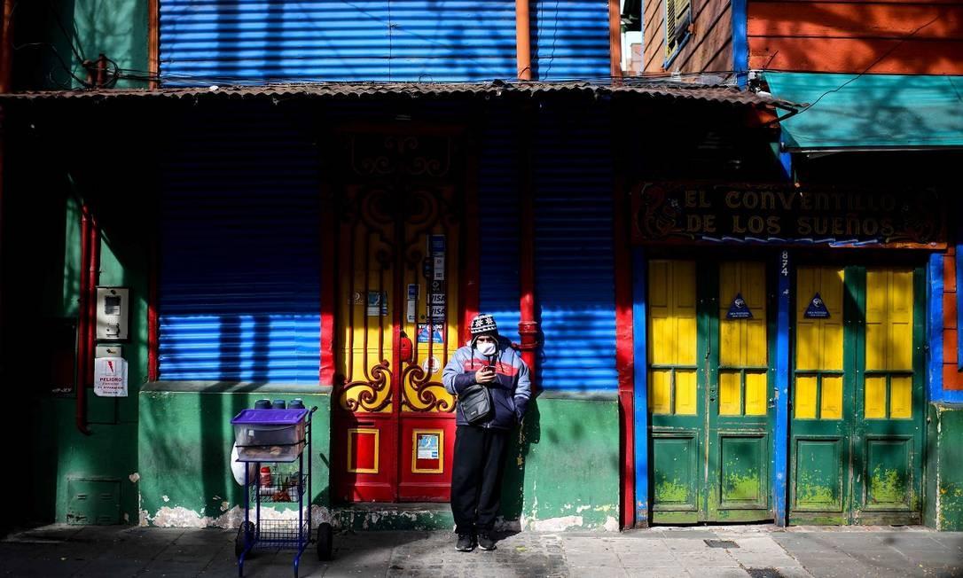 Um solitário vendedor de café em frente a uma loja fechada no bairro de La Boca, um dos que mais sofrem com a ausência de turistas em Buenos Aires durante a pandemia Foto: RONALDO SCHEMIDT / AFP