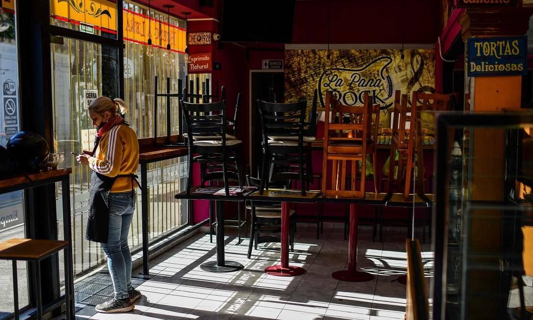 Funcionária de um restaurante vazio no bairro de La Boca, em Buenos Aires Foto: RONALDO SCHEMIDT / AFP
