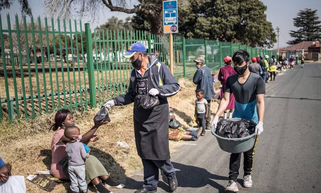 Voluntárias distribuem comida durante almoço especial em comemoração ao Dia Mandela, em Joanesburgo, no último sábado Foto: MARCO LONGARI / AFP