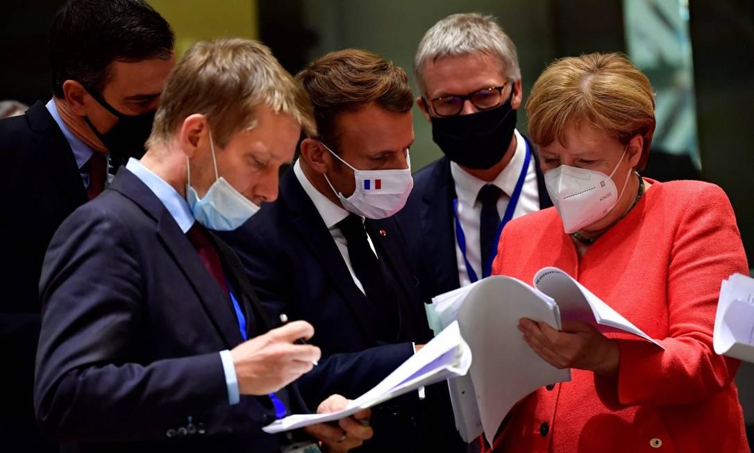 Primeiro-ministro da Espanha, Pedro Sanchez (esquerda), presidente francês Emmanuel Macron (centro) e chanceler alemã Angela Merkel observam documentos Foto: JOHN THYS / AFP