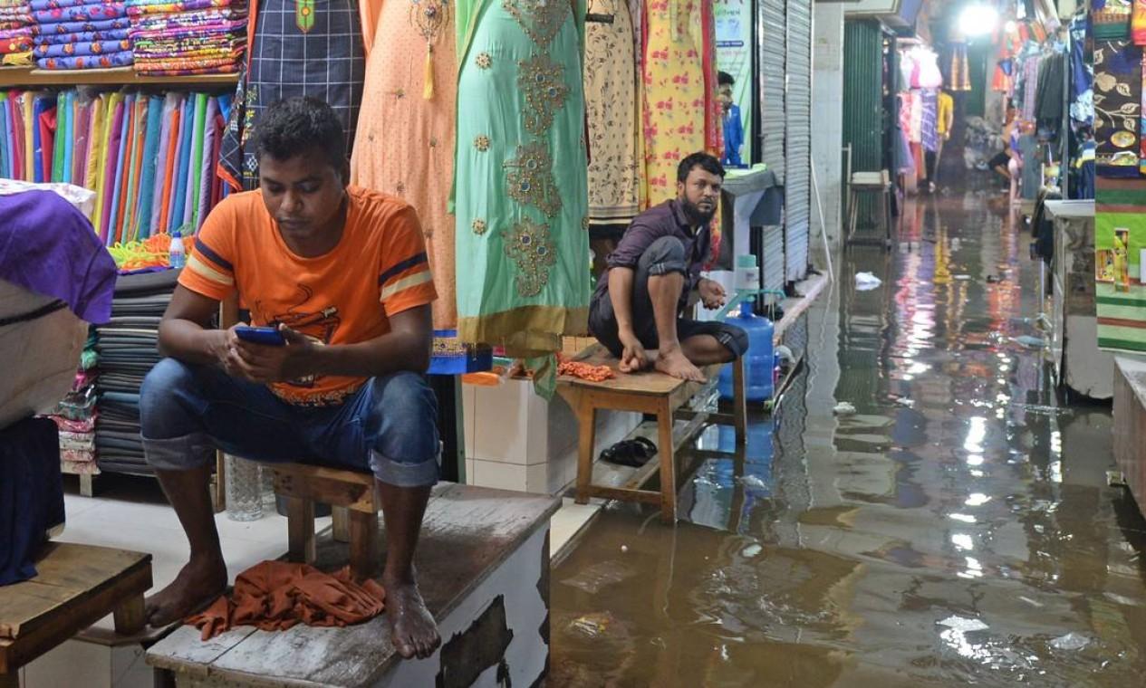 Lojistas esperam por clientes em um shopping cheio de água, após uma forte chuva, em Daca, Bangladesh. O número de mortos por fortes chuvas de monções no sul da Ásia subiu para quase 200, disseram autoridades Foto: MUNIR UZ ZAMAN / AFP