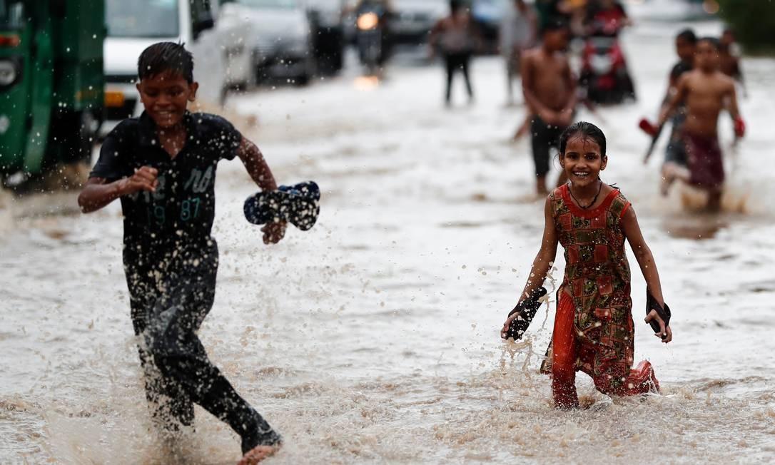 Crianças brincam em rua alagada de Nova Déli, capital da Índia Foto: ADNAN ABIDI / REUTERS