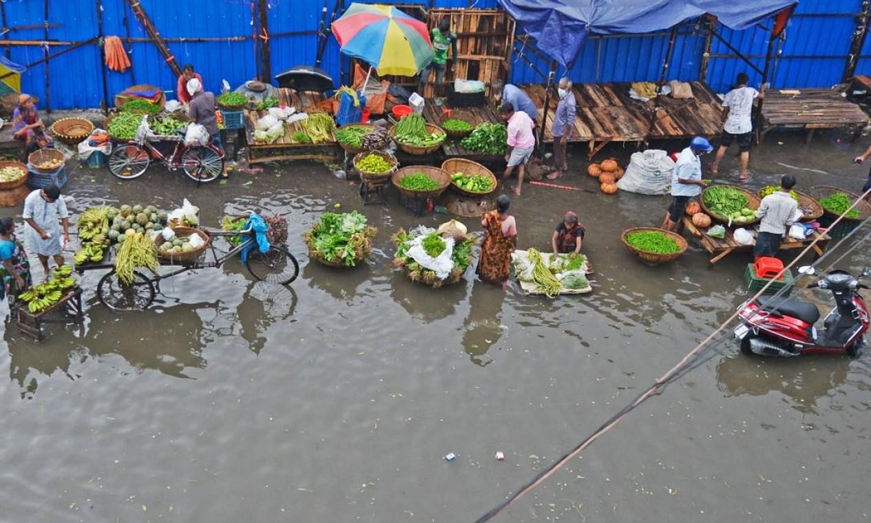 Os fornecedores de vegetais aguardam os clientes enquanto se sentam em uma rua cheia de água após uma forte chuva em Daca, Bangladesh Foto: MUNIR UZ ZAMAN / AFP