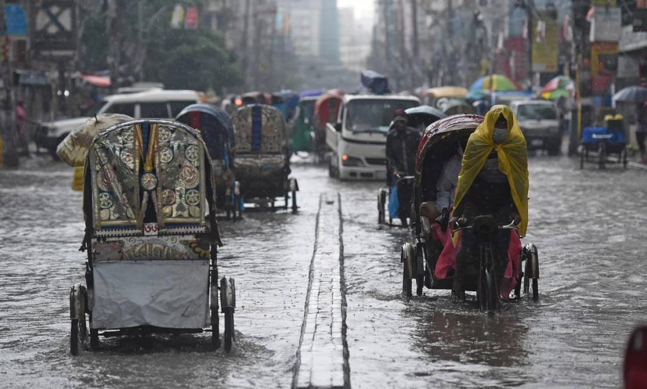 Puxadores de riquixá atravessam uma rua cheia de água após uma forte chuva em Daca, Bangladesh Foto: MUNIR UZ ZAMAN / AFP