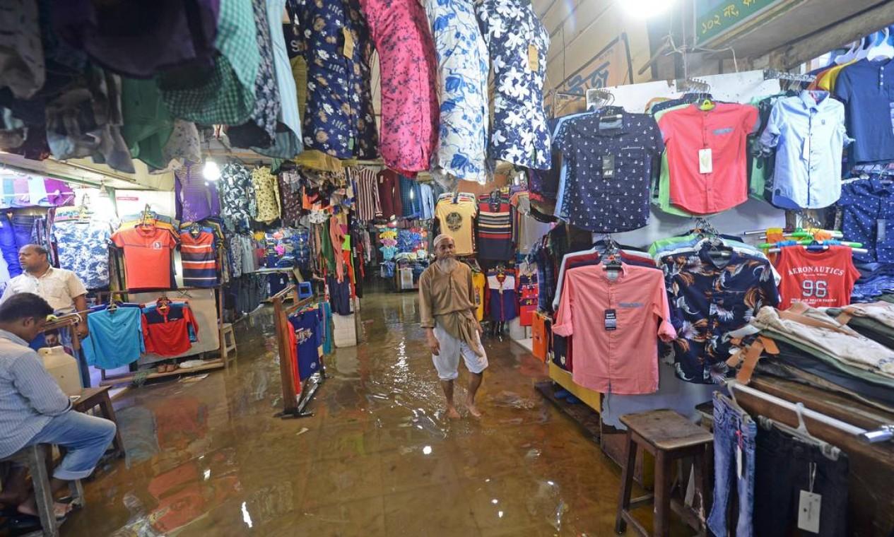 Um homem entra em um shopping cheio de água após uma forte chuva em Daca, Bangladesh Foto: MUNIR UZ ZAMAN / AFP