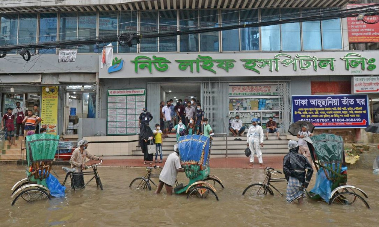 Puxadores de riquixá aguardam passageiros em uma rua cheia de água após uma forte chuva em Daca, Bangladesh Foto: MUNIR UZ ZAMAN / AFP