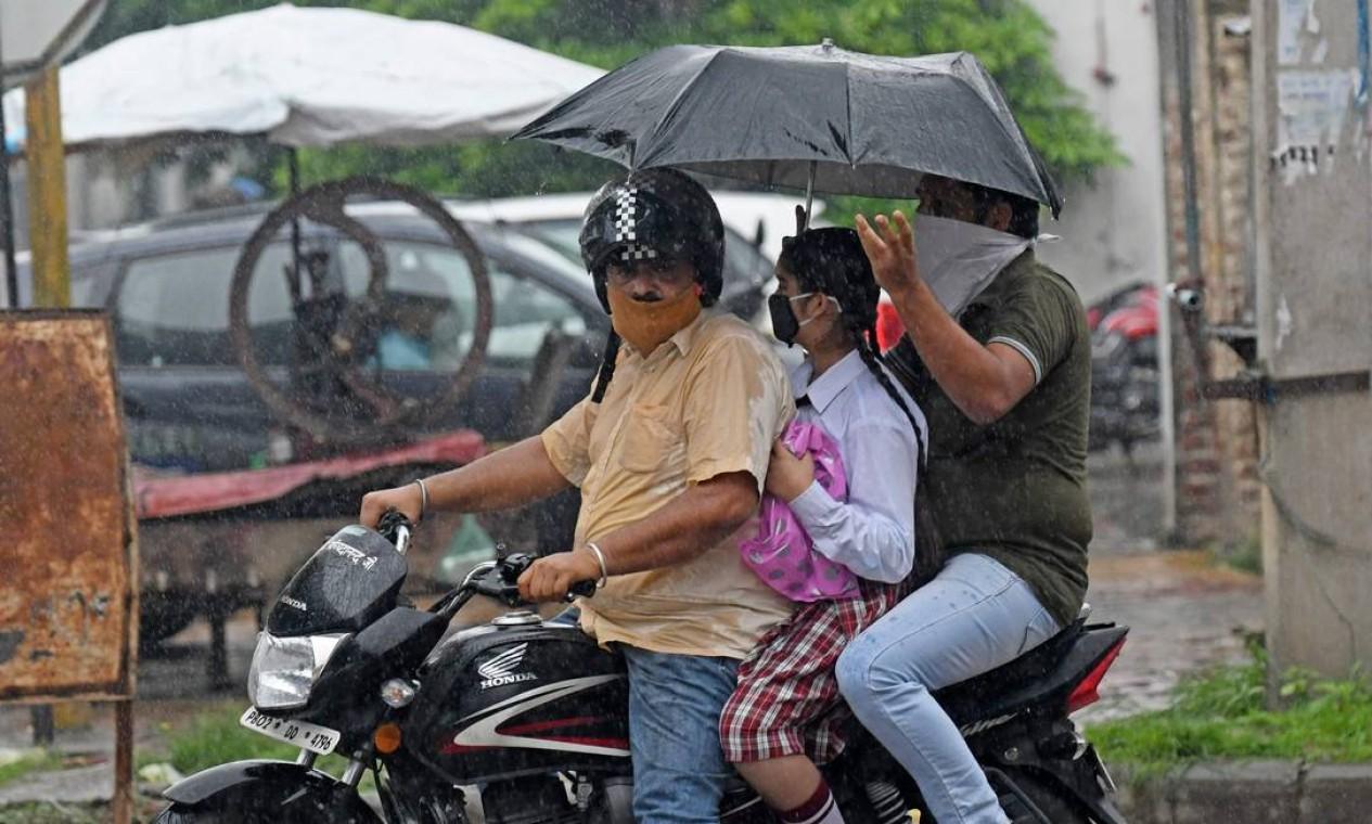 Os passageiros andam de moto durante uma chuva em Amritsa, na Índia Foto: NARINDER NANU / AFP