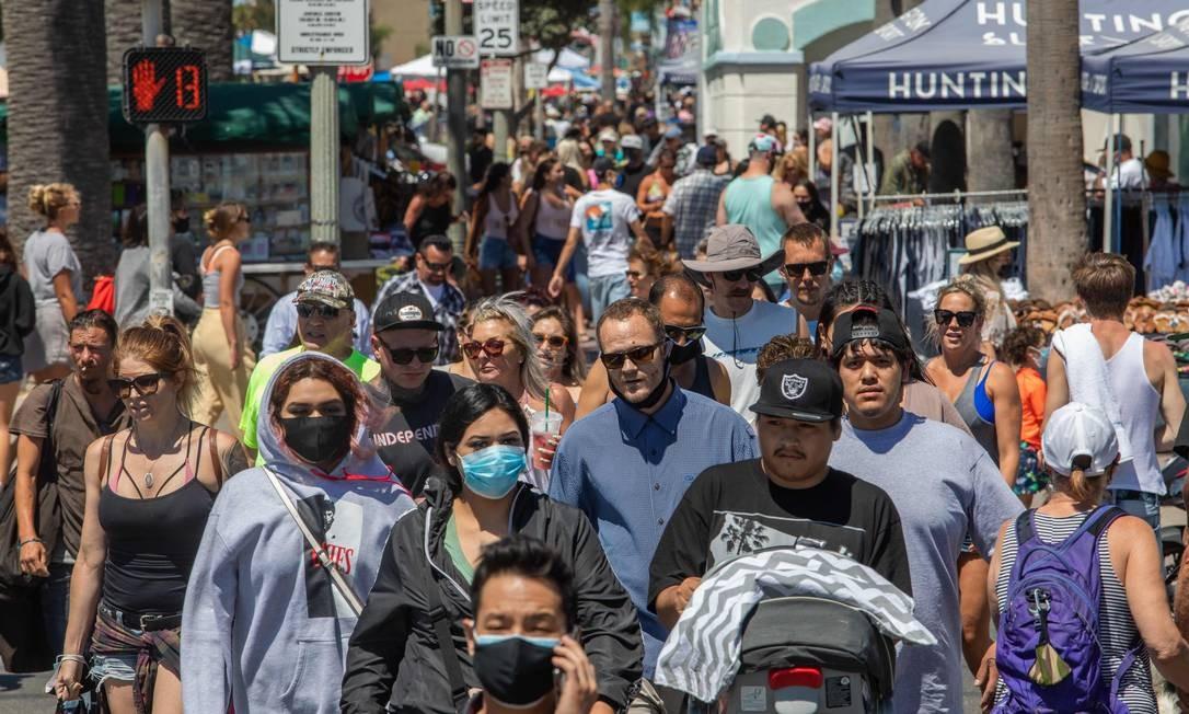 Pessoas andam pelas ruas da cidade de Huntington Beach, na Califórnia Foto: APU GOMES / AFP