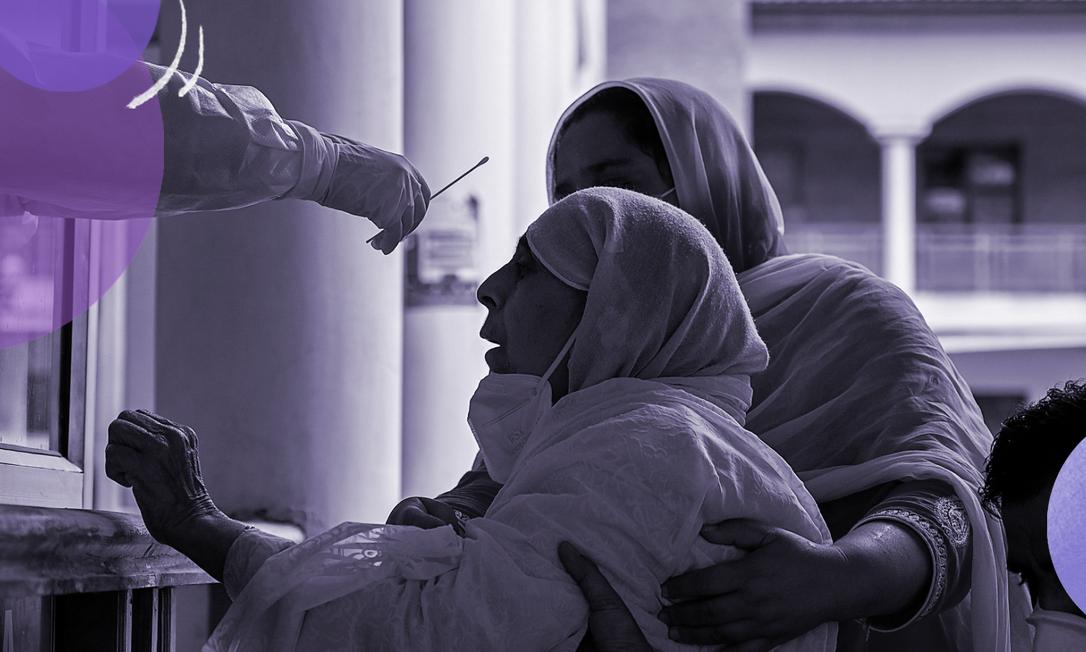 Idosa é ajudada por parentes na hora de fazer o teste da Covid-19 em Srinagar, na Índia: mulheres são mais afetadas pela pandemia Foto: TAUSEEF MUSTAFA / AFP