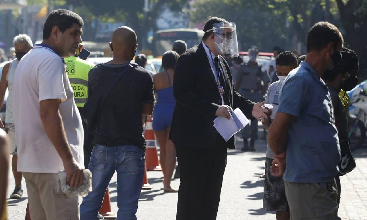 Funcionário da Caixa Econômica Federal, usando máscara protetora e escudo facial, atende pessoas na fila Foto: Fabiano Rocha / Agência O Globo