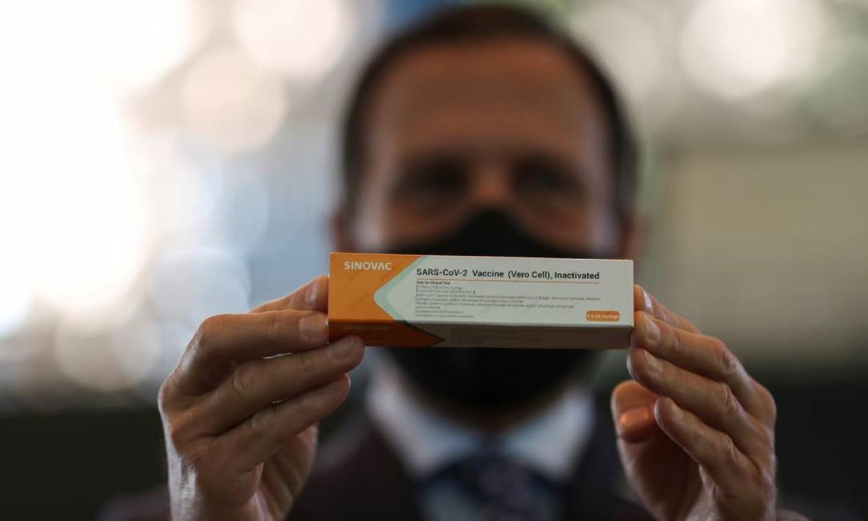 O governador do estado de São Paulo, João Doria, segura uma caixa da potencial vacina contra o coronavírus Sinovac da China para testes durante uma entrevista coletiva no Hospital das Clinicas, em São Paulo Foto: AMANDA PEROBELLI / REUTERS