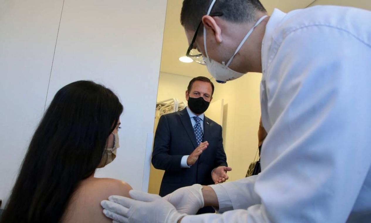 Governador de São Paulo, João Doria, aplaude voluntária que recebe a vacina chinesa Foto: HANDOUT / AFP