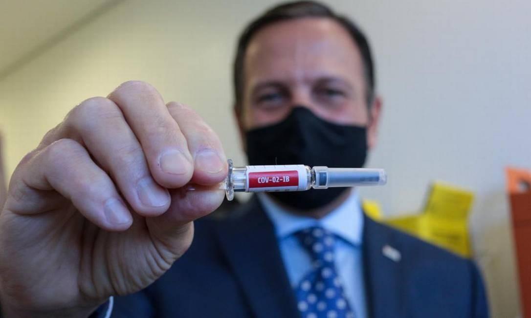 Governador do estado de São Paulo, João Doria, exibe seringa com dose da potencial vacina produzida pela empresa chinesa Sinovac Biotech Foto: HANDOUT / AFP