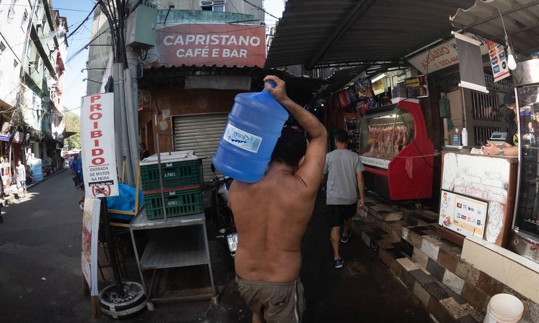 Localidade na parte baixa da comunidade está sem água há oito dias: moradores têm comprado galões ou recorrido a uma torneira na rua Foto: Roberto Moreyra / Agência O Globo