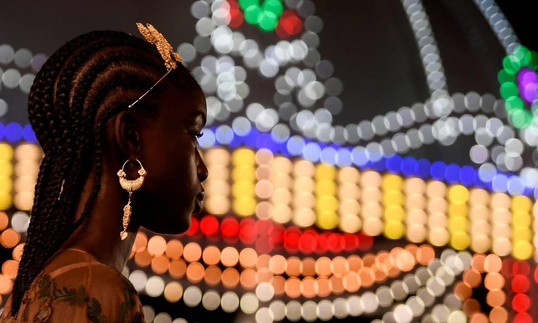 Moelo aparece com delicada tiara e, ao fundo, milhares de luzes que transformaram a Piazza del Duomo, na noite de quarta-feira (22) Foto: FILIPPO MONTEFORTE / AFP