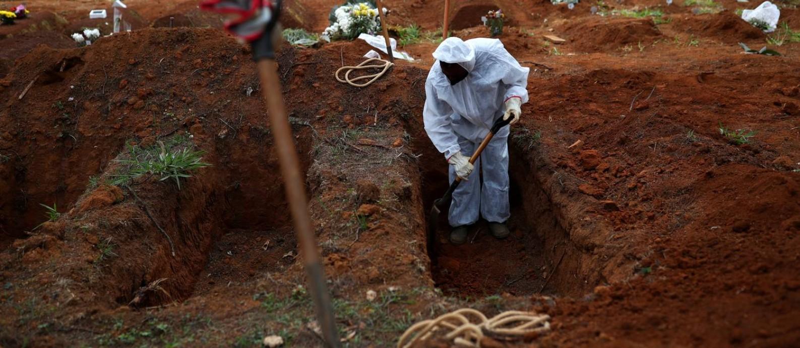 Coveiro com roupas de proteção cava cova para vítima da Covid-19 no cemitério de Vila Formosa, em São Paulo (SP), no último dia 16 Foto: AMANDA PEROBELLI / REUTERS