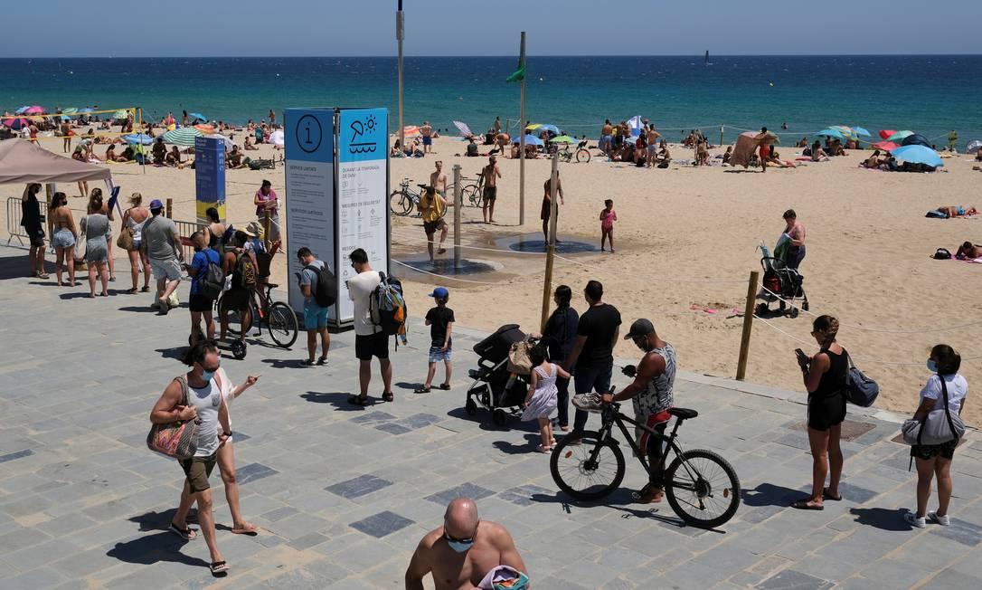 Pessoas fazem fila para entrar na praia, após região da Catalunha anunciar novas medidas de combate ao coronavírus Foto: Nacho Doce / REUTERS/19-07-2020