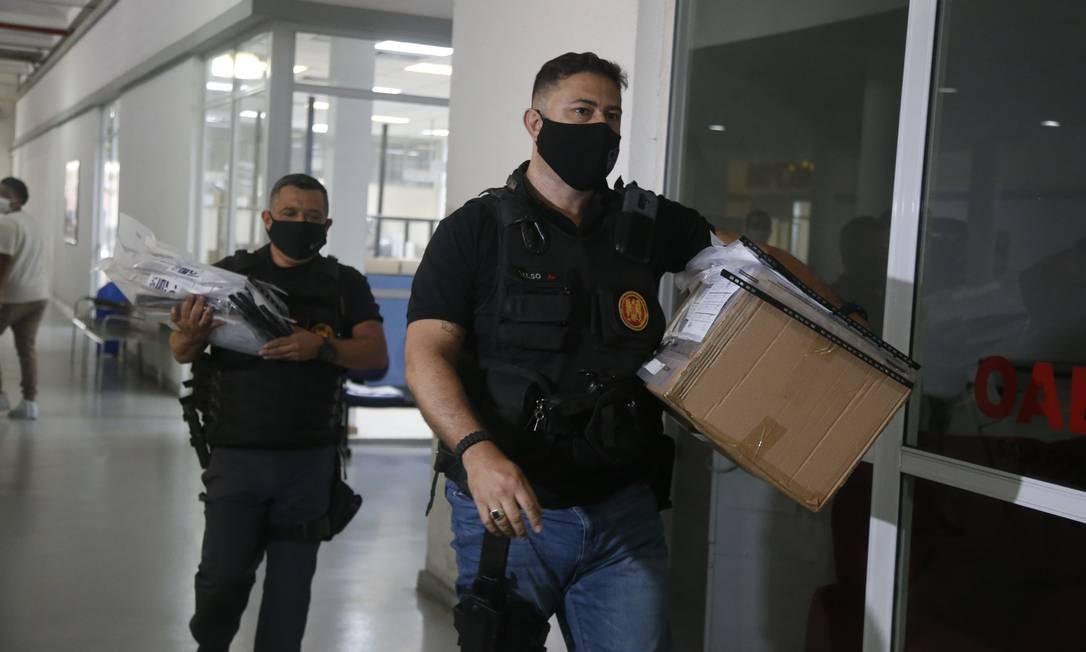 Policial carrega malotes apreendido durante operação realizada nesta quinta-feira Foto: Fabiano Rocha / Fabiano Rocha