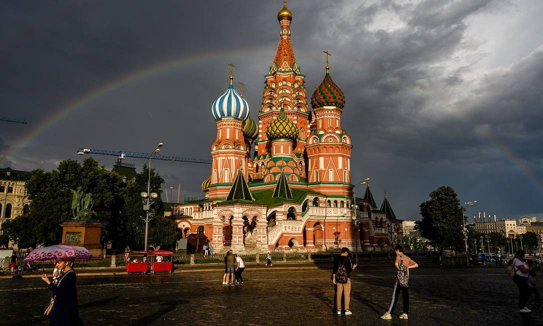 Pessoas caminham em frente à Catedral de São Basílio, na Praça Vermelha, em Moscou Foto: Dimitar Dilkoff / AFP