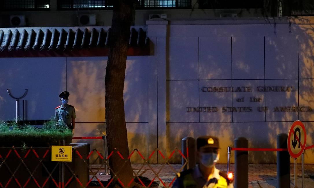 Policiais chineses montam guarda em frente ao consulado americano em Chengdu, que foi cercado por curiosos Foto: THOMAS PETER / REUTERS