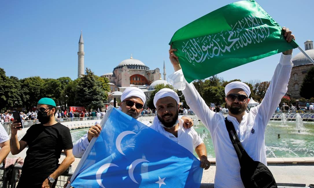 Pessoas seguram bandeiras enquanto esperam o início das orações de sexta-feira do lado de fora da Grande Mesquita Hagia Sophia, pela primeira vez depois que foi novamente declarada mesquita após 86 anos Foto: UMIT BEKTAS / REUTERS
