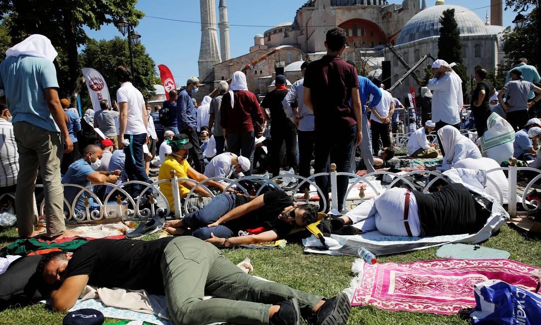 Pessoas esperam o início das orações de sexta-feira do lado de fora da Grande Mesquita Hagia Sophia, pela primeira vez depois que ela foi declarada novamente uma mesquita após 86 anos, em Istambul, Turquia Foto: UMIT BEKTAS / REUTERS