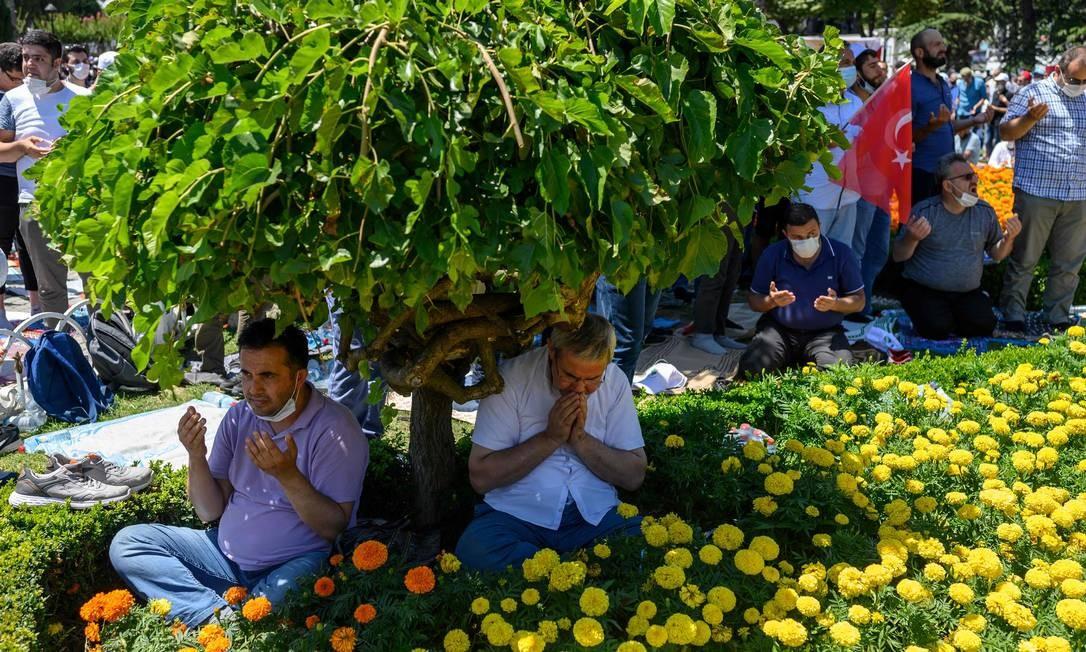 Pessoas se reúnem para a oração de sexta-feira, nos arredores de Hagia Sophia Foto: BULENT KILIC / AFP