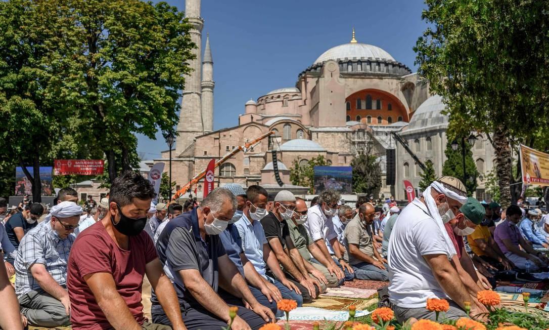 Homens realizam a oração de sexta-feira, nos arredores de Hagia Sophia, em Istambul, a primeira oração muçulmana realizada no ponto de referência desde que foi reconvertida em uma mesquita, apesar da condenação internacional Foto: BULENT KILIC / AFP