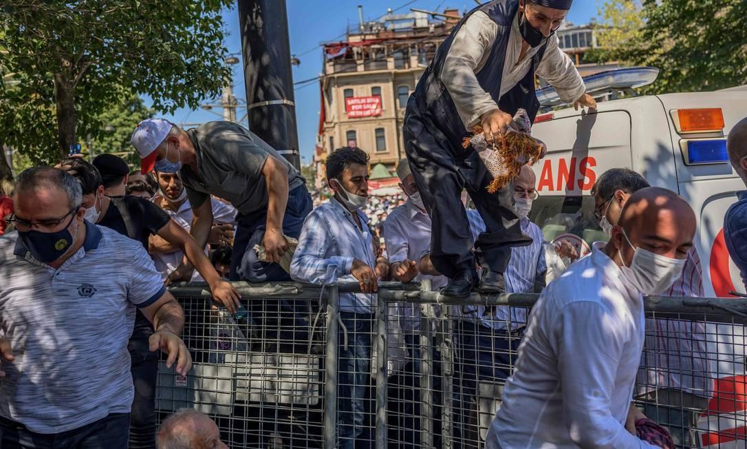 Homens correm por cima de cercas quando chegam para a oração de sexta-feira, nos arredores de Hagia Sophia Foto: BULENT KILIC / AFP