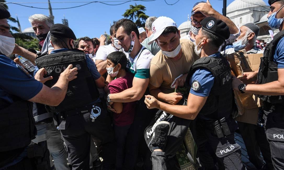 A polícia turca briga com um pequeno grupo de fiéis tentando entrar na praça superlotada do histórico distrito de Sultanahmet, em Istambul, enquanto milhares de pessoas se reúnem fora de Hagia Sophia para realizar a oração de sexta-feira Foto: OZAN KOSE / AFP
