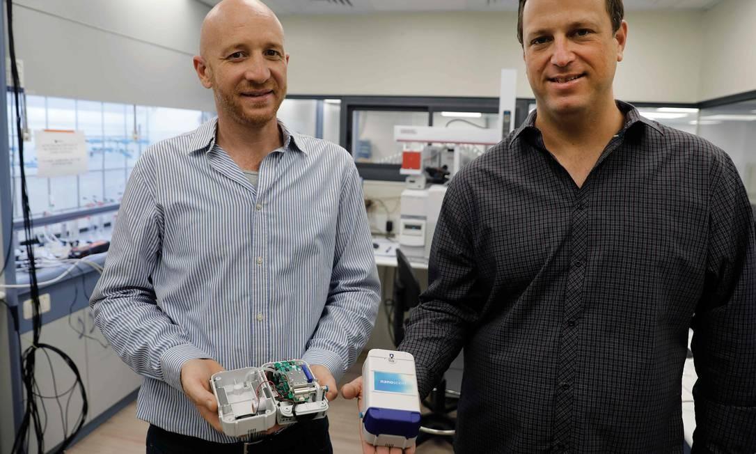 """O CEO, Oren Gavriely (esquerda) e o vice-presidente de Hardware, Yair Paska, posam com o """"Scent Reader"""", dispositivo usado para analisar amostra de respiração de um teste de bafômetro de coronavírus Foto: MENAHEM KAHANA / AFP"""