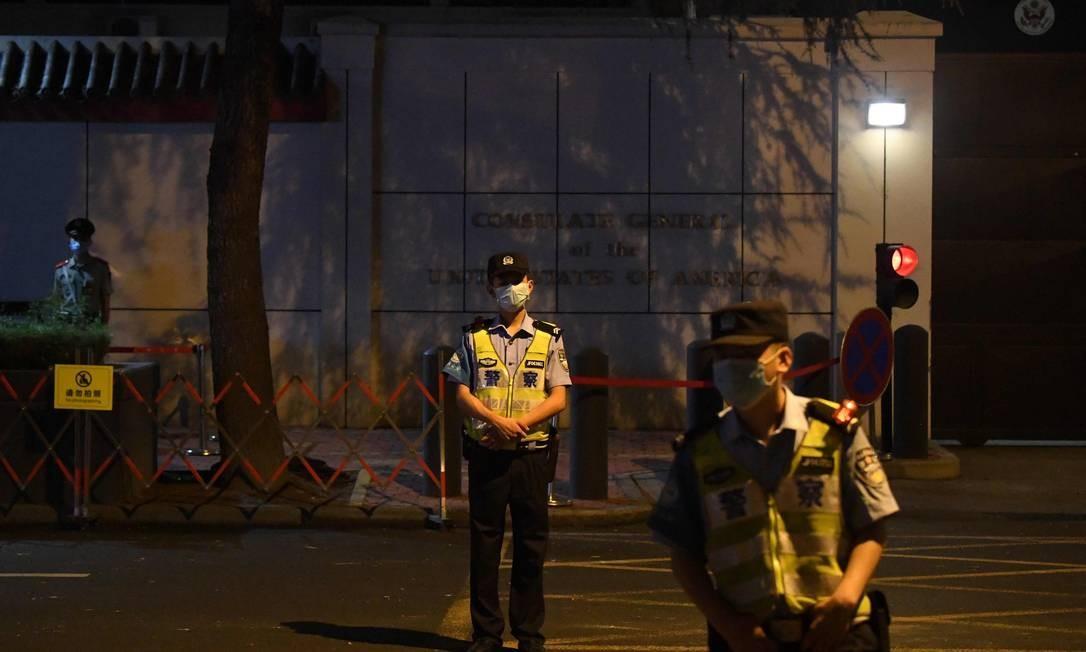 Policiais chineses montam guarda em frente ao consulado americano em Chengdu, que foi cercado por curiosos Foto: NOEL CELIS / AFP