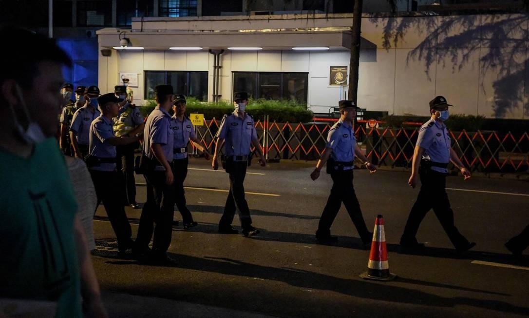 Policiais chineses vigiam o entorno do consulado americano em Chengdu Foto: NOEL CELIS / AFP