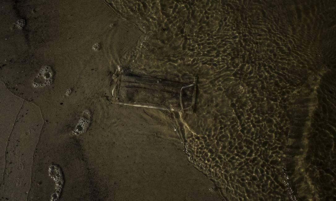 Máscara descartada na areia da enseada de Botafogo, na Zona Sul Foto: Guito Moreto / Agência O Globo