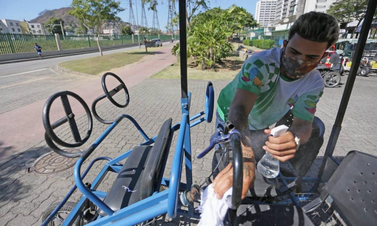 Trabalhador desinfeta triciclo, antes de ser alugado, no Parque Madureira Foto: Cléber Júnior / Agência O Globo
