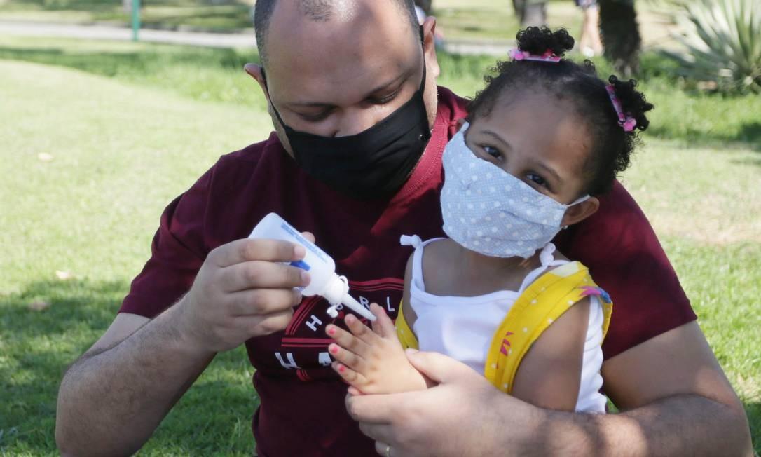 Jorge Luiz desinfeta as mãos da filha, durante passeio no Parque Madureira, na Zona Norte do Rio Foto: Cléber Júnior / Agência O Globo