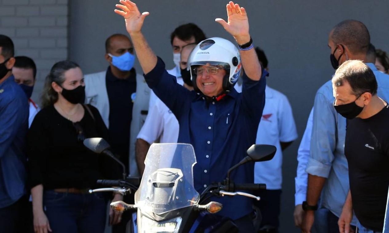 Bolsonaro acena sorridente de cima de sua moto Foto: Jorge William / Agência O Globo