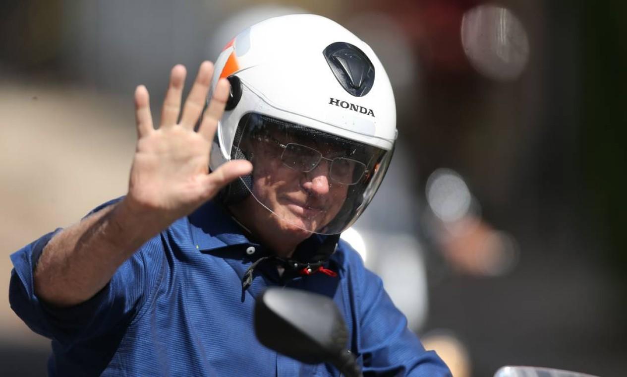 Presidente Jair Bolsonaro acena, pilotando moto, em Brasília Foto: Jorge William / Agência O Globo