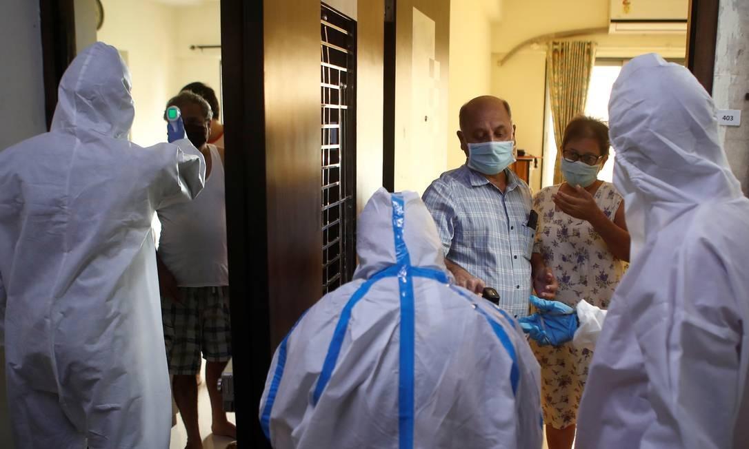 Profissionais de saúde medem a temperatura de moradores de Mumbai, na Índia, durante uma campanha de combate ao novo coronavírus. Foto: FRANCIS MASCARENHAS / REUTERS