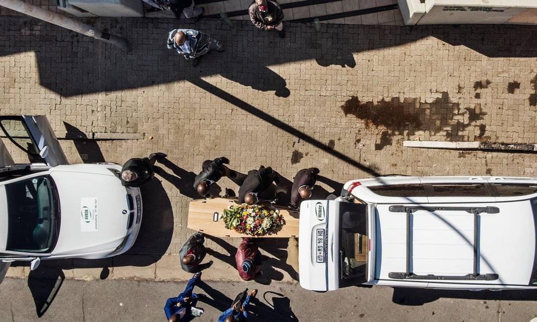 Parentes e funcionários de funerária carregam caixão de vítima da Covid-19 em Johannesburgo, na África do Sul, no último domingo (26); país é o quinto mais afetado pelo coronavírus no mundo Foto: MARCO LONGARI / AFP